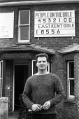 Jack Young, with mass unemployment figures displayed on his house, East Kent 1985 - NLA - 1980s,1985,activist,activists,against,CAMPAIGNING,CAMPAIGNS,DEMONSTRATING,Demonstration,figure,figures,house,houses,Jack Young,jobless,jobseeker,jobseekers,male,man,Marginalised,mass,men,numbers,peopl