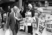 Gordon McLennan, gen sec of the Communist Party, 1985 walking past protest from his own party calling for more democracy outside a conference of the party in Hammersmith, West London. The party was in... - Peter Arkell - 1980s,1985,39th Special Congress,activist,activists,against,CAMPAIGNING,CAMPAIGNS,communism,Communist Party,conference,conferences,CPGB,democracy,Democracy not Bureaucracy,DEMONSTRATING,Demonstration,