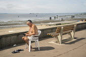 Man reading his ipad, Southend beach, Essex. - Jess Hurd - 08-08-2019