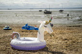 Unicorn inflatable, Southend, Essex. - Jess Hurd - 2010s,2019,beach,BEACHES,CHILD,CHILDHOOD,children,COAST,Essex,holiday,HOLIDAYS,inflatable,juvenile,juveniles,kid,kids,Leisure,LFL,LIFE,Lifestyle,OCEAN,PEOPLE,play,PLAYING,RECREATION,RECREATIONAL,rural