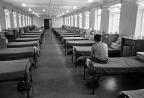 Youth in the dormitory, Send Detention Centre, Woking, Surrey, 1979. Short, sharp shock correction centre. - Martin Mayer - 1970s,1979,adolescence,adolescent,adolescents,alone,boy,boys,child,CHILDHOOD,children,CLJ,Crime,criminal,Criminal Justice System,criminalisation,criminalise,criminalize,criminals,custody,detainee,deta