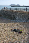 Young man sleeping on a pebble beach, luxury cruise liner, Western Harbour, Dover, Kent - Philip Wolmuth - 15-08-2019