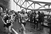 Runners in the first London Marathon over Tower bridge.1981 Sponsored by Gillette - Katalin Arkell - 1980s,1981,1st,amateur,amateurs,cities,City,first,First London marathon,highway,hobbies,hobby,hobbyist,leg,legs,Leisure,LFL,LIFE,London,long distance,marathon,marathons,PEOPLE,PHYSICAL,race,RECREATION