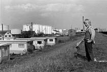Boy with a kite, caravan park and LNG storage tanks, 1974, Thorney Bay, Canvey Island, Thames Estuary - NLA - 1970s,1974,boy,boys,British Gas Corporation Liquified Natural Gas Terminal,Canvey Island,caravan,Caravan Site,caravans,child,childhood,children,EBF,Economic,Economy,ENI,environment,Environmental Issue