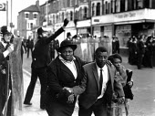 Family fleeing the Brixton riots, London 1981 as police try to restore order - Peter Arkell - 12-04-1981