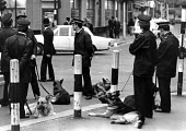 Police with dogs, Brixton, London, 1982, following a riot started by a police raid in the area - Peter Arkell - 1980s,1982,adult,adults,alsatian,alsatians,animal,animals,Brixton,canine,cities,City,CLJ,dog,dogs,force,London,Metropolitan Police Service,OFFICER,officers,patrol,patrolling,Police,Police Dog,Police d