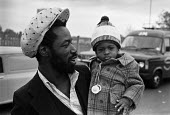 Black father with son on the picket line, Ford strike, Dagenham, London 1978 - Peter Arkell - 1970s,1978,Black father,boy,boys,child,childhood,children,DAD,DADDIES,DADDY,DADS,Dagenham,DISPUTE,DISPUTES,EARLY YEARS,FAMILY,father,FATHERHOOD,fathers,Ford,Fords,infancy,infant,infants,London,male,ma