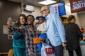 Jeremy Corbyn with supporters in Greggs, Big Canvass with Jeremy Corbyn and Faiza Shaheen, PPC, Chingford and Woodford Green, Iain Duncan Smith constituency. London. - Jess Hurd - 2010s,2019,BAME,BAMEs,Big Canvass,Black,Black and White,BME,bmes,CAMERA,camera phone,cameras,campaign,campaigning,CAMPAIGNS,CANVASING,canvassing,Chingford and Woodford Green,Chingford Mount,constituen