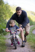 Farther helping daughter to learn to ride a bike, Bangeston, Angle, Pembrokeshire - Paul Box - 2010s,2018,assisting,bicycle,bicycles,BICYCLING,Bicyclist,Bicyclists,bike,bikes,care,caring,cycle,cycles,cycling,Cyclist,Cyclists,daughter,DAUGHTERS,FAMILY,Farther,FATHER,FATHERHOOD,from,help,helping,