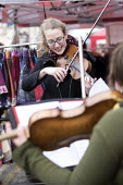 Buskers playing violin, Tobacco factory Market, Bristol - Paul Box - 2010s,2016,ACE,Arts,bought,Bristol,buy,buyer,buyers,buying,cities,City,consumer,consumers,Culture,customer,customers,FACTORIES,factory,FEMALE,market,market stall,market stalls,markets,melody,music,MUS