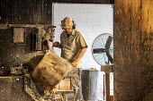 Michigan, USA: Worker shaping log with a laith, The Holland Bowl Mill, which manufactures bowls and other wood products - Jim West - 2010s,2019,bowl making,by hand,capitalism,craft,craftsman,dust,dusty,EBF,Economic,Economy,employee,employees,Employment,FACTORIES,factory,handmade,hardwood,hazard,hazardous,hazards,Health and Safety,H