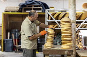 Michigan, USA: worker stacking wooden bowls, The Holland Bowl Mill, which manufactures bowls and other wood products - Jim West - 10-10-2019