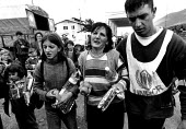 Kosovar Albanian refugees 1999 UNHCR worker helping them to cross the border. Molina, Kosovo - Albania border - Masanori Kobayashi - 03-05-1999