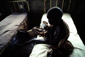 Famine, Ethiopia, 1984, Sudanese refugee child orphaned by the famine and war, Fugnido Orphanage Camp - Masanori Kobayashi - 1990,1990s,africa,African,Africans,bed,beds,camp,camps,child,CHILDHOOD,children,dia,Diaspora,disaster,DISASTERS,displaced,drought,east africa,ethiopia,Ethiopian,ethiopians,famine,famine malnourished h
