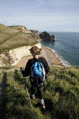 Young woman walking the South West Coast Path towards Durdle Door, Dorset - David Mansell - 2010s,2015,access,beach,BEACHES,Chalk,chalk headland,cliff,cliffs,coast,coastal,Coastal Erosion,coasts,COUNTRYSIDE,edge,eroded,erosion,female,footpath,footpaths,hiker,hikers,hiking,holiday,holidays,Ja