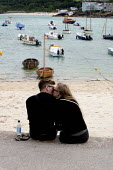 St Ives, Cornwall, a young couple kissing as they sit on the harbour sea wall - David Mansell - 2010s,2015,adult,adults,beach,BEACHES,COAST,cornwall,couple,COUPLES,defenses,FEMALE,harbor,harbors,harbour,harbours,holiday,holiday maker,holiday makers,holidaymaker,holidaymakers,holidays,kiss,kissin