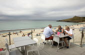 St Ives, Cornwall, family all on their mobile phones at a beach cafe overlooking the beach - David Mansell - 16-07-2015