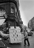Workers moving boxes of tomatos, Long Acre, Covent Garden 1973 before the market moved to Nine Elms - Martin Mayer - 1970s,1973,box,boxes,by hand,cart,carts,cities,City,Covent Garden,developer,developers,EBF,Economic,Economy,employee,employees,Employment,food,FOODS,fruit,fruits,Garden,GARDENS,job,jobs,LBR,London,Lon