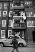 Boy playing, Brixton housing estate, London 1974. Morris Minor car - Martin Mayer - 02-05-1974