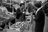 Fruit and Vegetable stall, Brixton street market, 1972 London - NLA - 1970s,1972,bought,Brixton,buy,buyer,buyers,buying,cash,cities,City,consumer,consumers,customer,customers,EBF,Economic,Economy,employee,employees,Employment,FEMALE,food,FOODS,Fruit and Vegetables,green