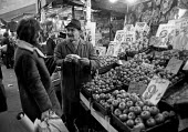 Fruit and Vegetable stall, Brixton street market, 1972 London - NLA - 1970s,1972,age,ageing population,apple,apples,bought,Brixton,buy,buyer,buyers,buying,cash,Christmas,cities,City,consumer,consumers,customer,customers,EBF,Economic,Economy,elderly,employee,employees,Em