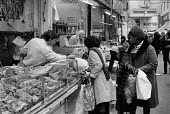 Shoppers, butchers stall, Brixton market, London 1972 - Peter Arkell - 1970s,1972,BAME,BAMEs,Black,black women,BME,bmes,bought,Brixton,butcher,butchers,buy,buyer,buyers,buying,cities,City,consumer,consumers,customer,customers,diversity,EBF,Economic,Economy,employee,emplo