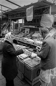 Buying eggs from a stall, Brixton market, London 1972 - Peter Arkell - 1970s,1972,age,ageing population,bought,Brixton,Brixton market,buy,buyer,buyers,buying,cities,City,consumer,consumers,customer,customers,EBF,Economic,Economy,egg,egg stall,Eggs,elderly,employee,employ