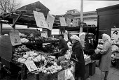 Shoppers, fruit and vegetable stall, Brixton market, London 1972 - Peter Arkell - 1970s,1972,bought,Brixton,Brixton market,buy,buyer,buyers,buying,cities,City,consumer,consumers,customer,customers,EBF,Economic,Economy,employee,employees,Employment,FEMALE,food,FOODS,Fruit and Vegeta