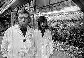 Young workers, Dewhurst the Butchers, Brixton, London 1972 - Peter Arkell - 1970s,1972,Brixton,Butcher,butchers,cities,City,Dewhurst,EARNINGS,EBF,Economic,Economy,employee,employees,Employment,food,FOODS,Income,job,jobs,LBR,London,Low Pay,Low Income,low paid,Low Pay,male,man,