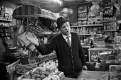 Traditional greengrocer, Islington, London 1972. Danny Doolan in his well stocked shop a few months before he had to close due to competition from supermarkets - Peter Arkell - 1970s,1972,cities,City,COMPETITATIVE,competition,competitor,competitors,Corner Shop,Danny Doolan,EBF,Economic,Economy,employee,employees,Employment,food,FOODS,Fruit and Vegetables,greengrocer,Islingto