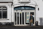 Shopper in the doorway of closed BHS Store, Stratford upon Avon, Warwickshire. British Home Stores closed in 2016, MPs described billionaire retailer Sir Philip Green, who owned BHS from 2000 to 2015,... - John Harris - 2010s,2019,administration,alone,bag,bags,bankrupt,bankruptcy,BHS,billionaire,bought,British Home Stores,Bus Stop,Business,buying,Capitalism,capitalist,close,closed,closing,closing down,closure,closure