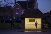 Woman waiting for a bus, Wellsbourne village, Warwickshire - John Harris - 2010s,2019,alone,bus,bus service,Bus Stop,buses,darkness,EBF,Economic,Economy,evening,FEMALE,highway,journey,JOURNEYS,lone,lonely,night time,PEOPLE,person,persons,road,roads,roadside,rural,service,ser