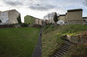 Youth walking through a housing estate, Hazel Leys, Corby, Northamptonshire - John Harris - 2010s,2019,adolescence,adolescent,adolescents,boy,boys,child,CHILDHOOD,children,Council Housing,Council Housing,estate,ESTATES,excluded,exclusion,flat,flats,HARDSHIP,house,houses,housing,Housing Estat