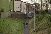Youth walking through a housing estate, Hazel Leys, Corby, Northamptonshire - John Harris - 2010s,2019,child,CHILDHOOD,children,Council Housing,Council Housing,estate,ESTATES,excluded,exclusion,female,females,flat,flats,girl,girls,HARDSHIP,house,houses,housing,Housing Estate,impoverished,imp
