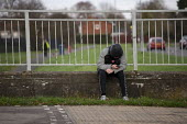 Youth on his mobile phone, Hazel Leys, Corby, Northamptonshire - John Harris - 2010s,2019,adolescence,adolescent,adolescents,anti social behavior,anti social behaviour,antisocial,antisocial behaviour,boy,boys,bullies,bully,bullying,CELLULAR,child,CHILDHOOD,children,ciberbullying