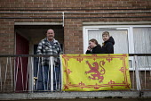 Proud Scoltsman with flag on his balcony; Corby; Northamptonshire. The Royal Standard of Scotland - John Harris - 2010s,2019,boy,boys,child,CHILDHOOD,children,Council Housing,Council Housing,DAD,DADDIES,DADDY,DADS,EMOTION,EMOTIONS,excluded,exclusion,father,FATHERHOOD,fathers,female,females,flag,flags,flat,flats,g
