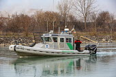 Detroit, Michigan USA. US Border Patrol boat cutting through ice on Conners Creek on its way to patrol the Detroit River between the United States and Canada. - Jim West - 2010s,2019,America,boat,boats,border,Border and Immigration Agency,border control,border controls,Border Patrol,borders,CAN124,Canada,Canadian border,CLJ,cutting,Detroit,Diaspora,enforcement,force,for