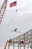 Detroit, Michigan USA. Construction workers raising a US flag and a Christmas tree on the last piece of structural steel to be placed on new Fiat Chrysler automobile assembly plant. It is the first ne... - Jim West - 13-12-2019