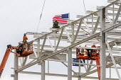 Detroit, Michigan USA. Construction workers raising a US flag and a Christmas tree on the last piece of structural steel to be placed on new Fiat Chrysler automobile assembly plant. It is the first ne... - Jim West - 1st,2010s,2019,America,american,americans,assembly,assembly plant,auto,auto factory,auto industry,auto plant,automobile,Automotive Industry,building,building site,buildings,CAR,car factory,cars,Christ