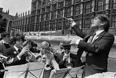 Musicians strike against the BBC closing down orchestras, London 1980 protest with musicians playing on a boat outside the Houses of Parliament - NLA - 1980,1980s,activist,activists,against,bands,BBC,boat,BOATS,Brass Band,CAMPAIGNING,CAMPAIGNS,cities,City,closing,concert,concerts,conducting,conductor,conductors,DEMONSTRATING,Demonstration,disputes,Ho