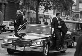 Motorcade carrying President Reagan, Whitehall, London 1984, as he travels to meet Margaret Thatcher in Downing Street, security agents - Peter Arkell - 1980s,1984,agent,agents,Cadillac,carries,carry,carrying,Limousine,limousines,London,POL,political,POLITICIAN,POLITICIANS,Politics,President,President Reagan,presidential motorcade,presidential state c