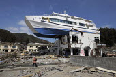A ship inland on the roof of a building. A survivor returning to seach the devastated Ootsuchi, (Otsuchi) Iwate prefecture, Earthquake and Tsunami, Japan - Kobayashi Masanori - 03-04-2011
