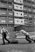Youth pushing a shopping trolly full of paving stones, derelict Netherley Estate, Liverpool, 1988. To sell to garden centre for A?1 each - Dave Sinclair - 12-04-1988