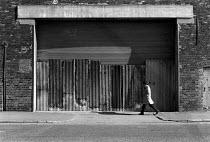 Man walking past closed Tate and Lyle, love Lane, Liverpool, 1983 - Dave Sinclair - 1980s,1983,Boarded Up,building,buildings,cities,City,closed,closing,closure,closures,deindustrialisation,deindustrialization,demolish,DEMOLISHED,demolishing,demolition,derelict,DERELICTION,DEVELOPMENT