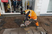 Worker cutting paving slabs, Stratford upon Avon, Warwickshire - John Harris - 2020,2020s,cut,cutter,cutters,cutting,Ear Protectors,EBF,Economic,Economy,employee,employees,Employment,groundwork,job,jobs,LBR,machine,machinery,machines,MAINTENANCE,male,man,men,pavement,pavingstone