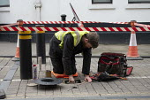 Worker repairing automatic rising bollard system, pedestrian zone, Stratford upon Avon, Warwickshire - John Harris - 2020,2020s,EBF,Economic,Economy,employee,employees,Employment,fix,fixing,job,jobs,LBR,maintaining,maintenance,male,man,men,pedestrian,PEDESTRIANS,people,person,persons,renovation,repair,repairing,REPA