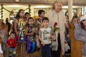 Detroit, Michigan USA, Holy Hour, supporting refugees fleeing violence, Most Holy Trinity Catholic Church.Mary Turner, right, escorting children bringing roses to the altar. The event was organized by... - Jim West - 11-01-2020