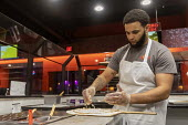 Detroit, Michigan, USA, worker making a pizza, Flamz Pizzeria. The restaurant makes pizzas to order with unlimited toppings, baked in a brick oven - Jim West - 2020,2020s,African American,African Americans,African-American,BAME,BAMEs,black,BME,bmes,brick,BRICKS,by hand,catering,chef,CHEFS,cook,COOKERY,cooking,cooks,Detroit,diversity,EARNINGS,EBF,Economic,Eco
