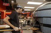 Detroit, Michigan, USA, worker baking a pizza, Flamz Pizzeria. The restaurant makes pizzas to order with unlimited toppings, baked in a brick oven - Jim West - 2020,2020s,African American,African Americans,African-American,bake,baking,BAME,BAMEs,black,BME,bmes,brick,brick oven,brick oven pizza,BRICKS,by hand,catering,chef,CHEFS,cook,COOKERY,cooking,cooking u