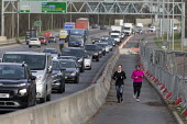 Joggers passing conjested traffic, A45 Coventry - John Harris - 2020,2020s,Air Pollution,Air Quality,AUTO,AUTOMOBILE,AUTOMOBILES,BAME,BAMEs,Black,BME,bmes,car,cars,CONGESTED,congestion,Coventry,diversity,driver,drivers,driving,ENI,environment,environmental degrada